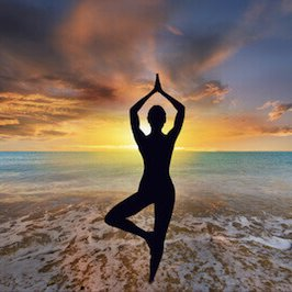 Young woman doing yoga exercise as the sun sets over the ocean